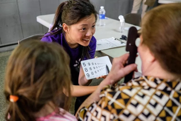 Erica Liao showing a patient and her daughter an eye chart
