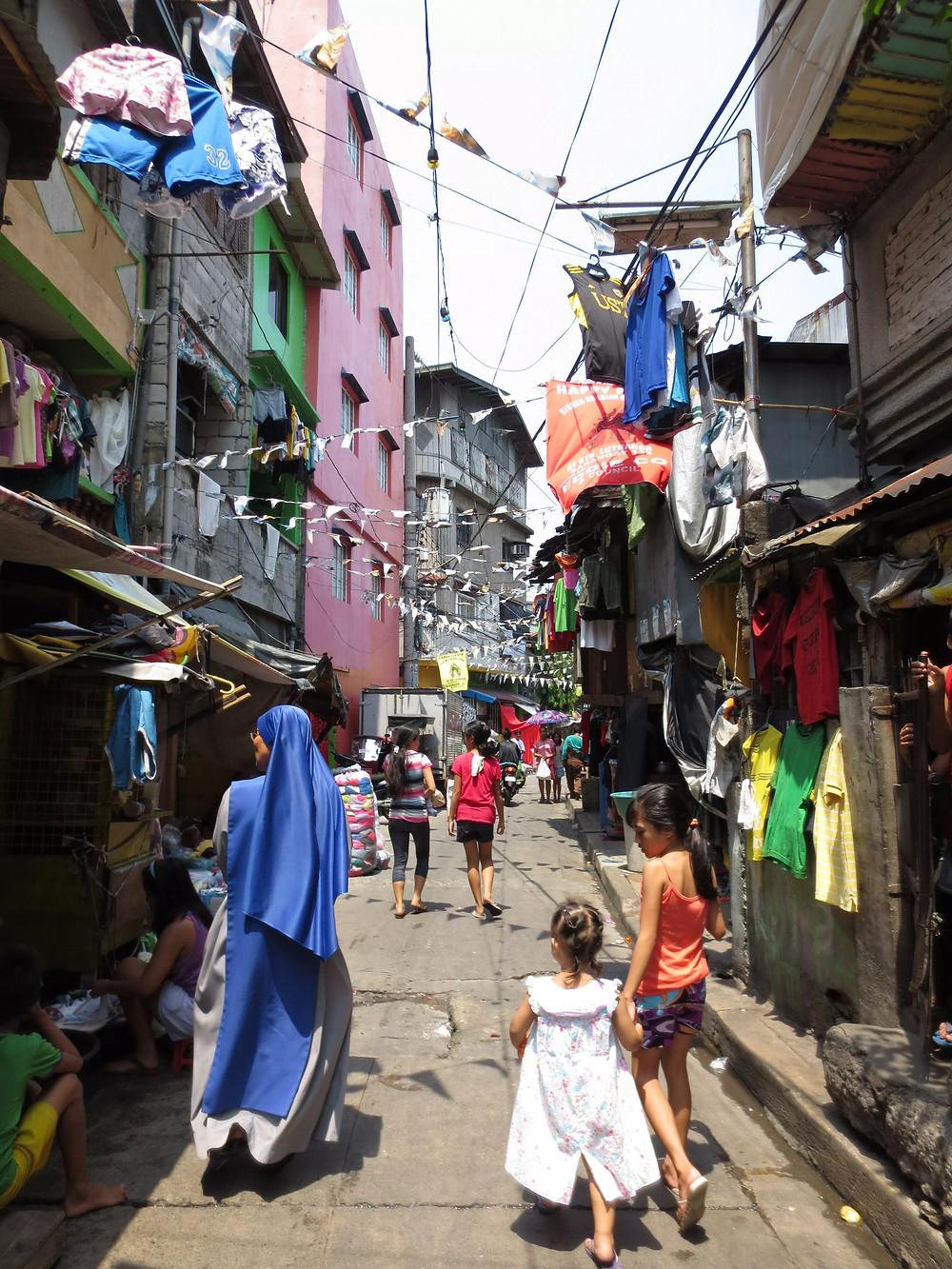 A nun walking in an alleyway in the Philippines.