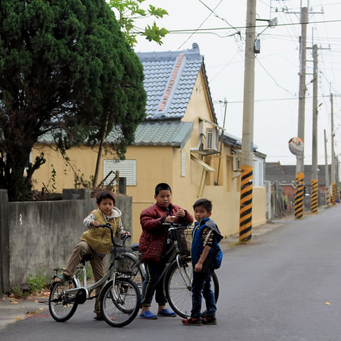 Two children stopped on their bikes and one child standing, all three looking at the camera. Background is of a Taiwanese road