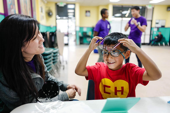 Hispanic child putting on three eyeglasses playfully