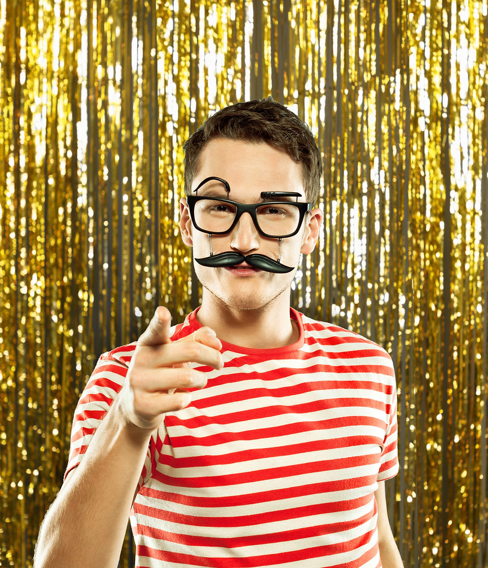 Man wearing plastic costume glasses and a moustache, a red stripe shirt, in front of a gold streamer background.