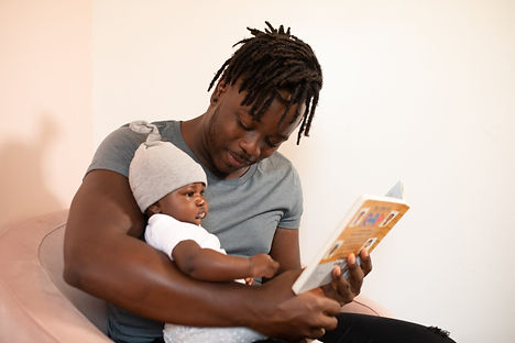 man-in-gray-shirt-holding-baby-in-white-