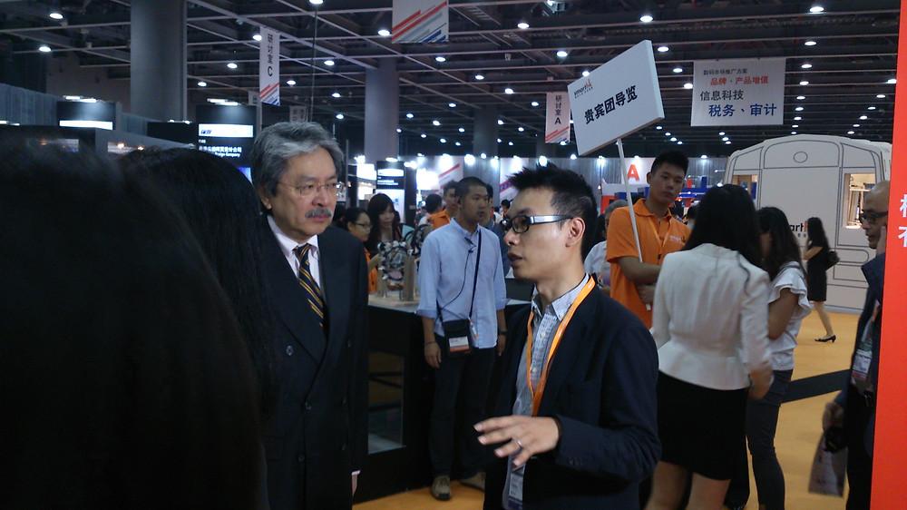 Kelvin (右)開設的公司透過貿發局「轉型升級‧香港博覽」(SmartHK) 接獲福建大型錶廠瑞達生意。左為財政司司長曾俊華。
