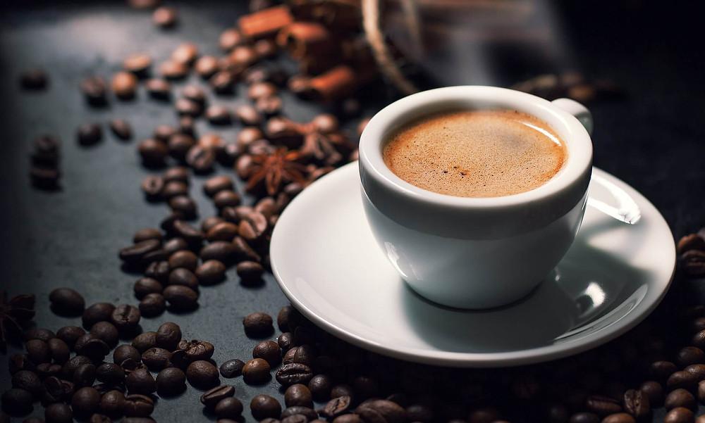 cốc cafe đặt trên bàn rải hạt cafe xung quanh