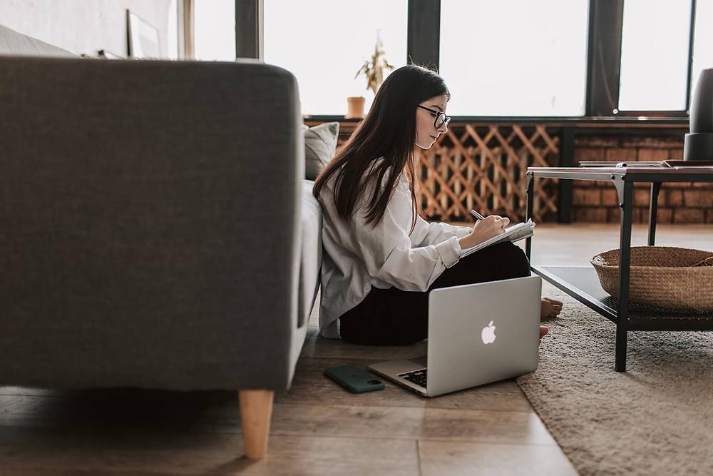 cô gái làm việc cùng laptop và sổ tay cạnh ghế sofa