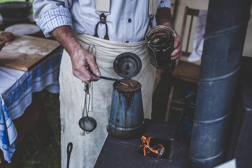 người đàn ông đang ủ cafe từ ấm đun
