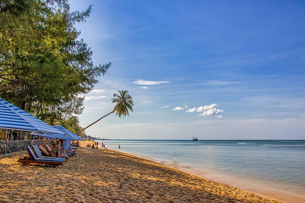 bãi biển ban ngày với ghế dài nghỉ ngơi cho khách