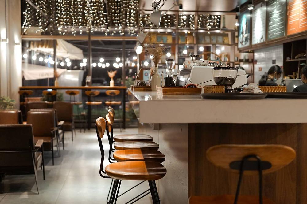 quầy pha chế của quán cafe với ghế ngồi và dụng cụ