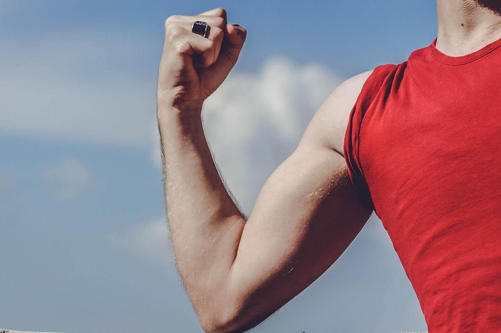 người đàn ông mặc áo đỏ gồng khoe cơ bắp