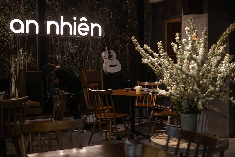 sân uống cà phê, bàn ghế và lọ hoa
