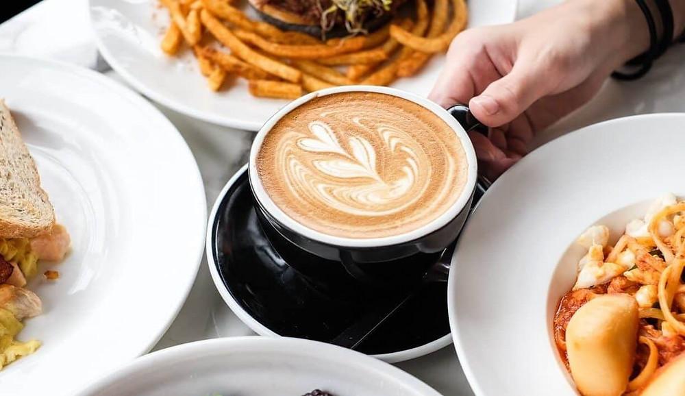cốc cafe Latte đặt giữa nhiều đĩa thức ăn