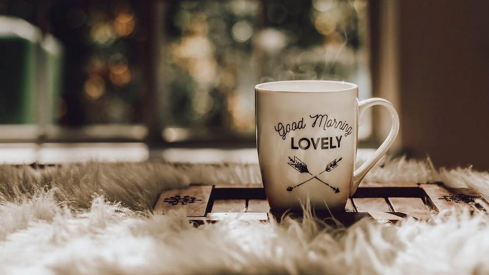 cốc cafe nóng đặt trên giường vào buổi sáng
