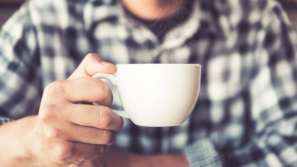 chàng trai đang cầm cốc cafe