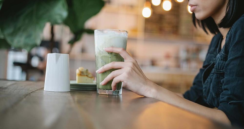 cô gái thưởng thức matcha latte tại quán cafe