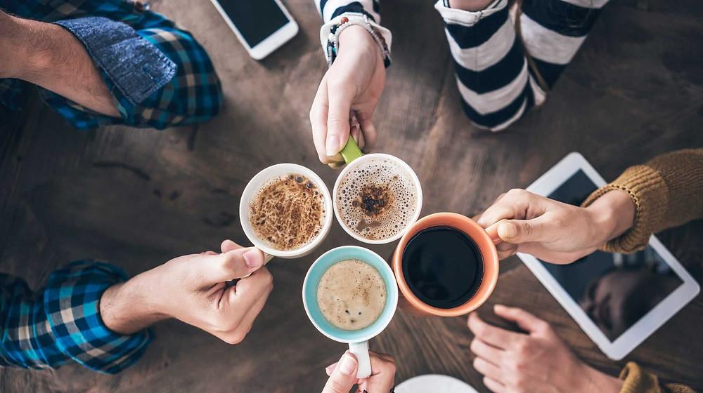 một nhóm bạn đang cụng ly uống cà phê