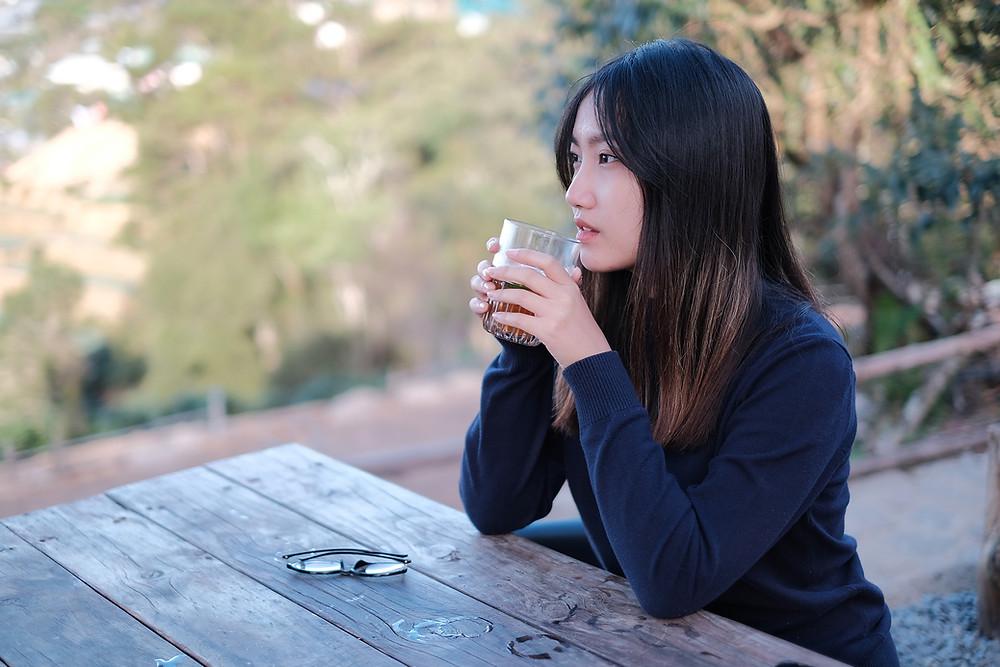 cô gái mỉm cười chuẩn bị uống trà