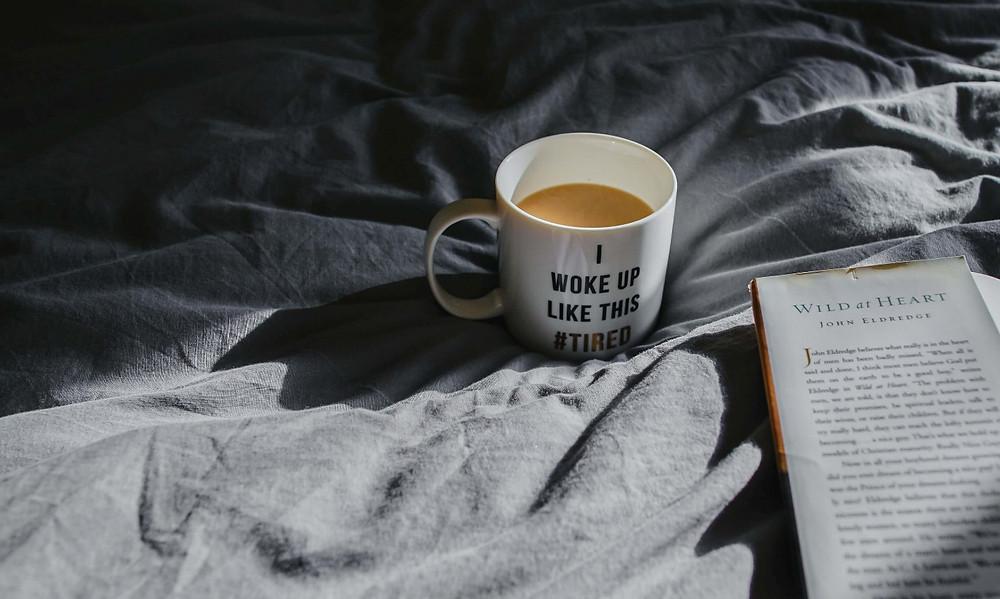 cốc cafe đặt cạnh cuốn sách trên giường