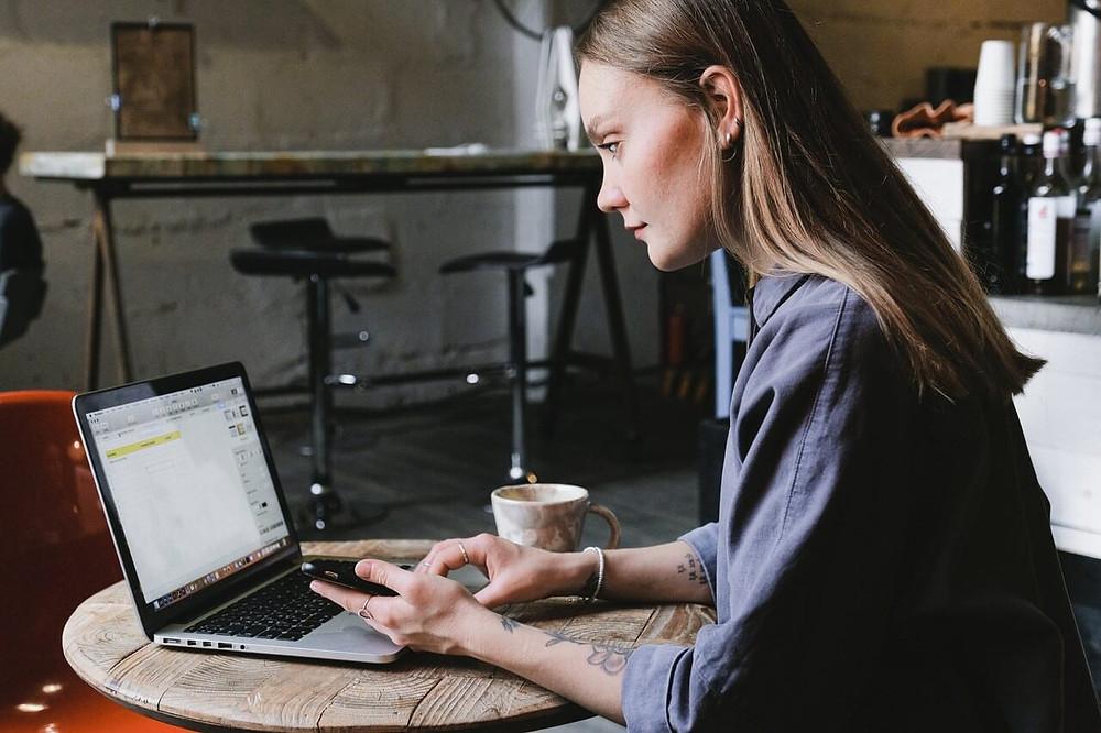 cô gái làm việc cùng laptop ở bàn cafe