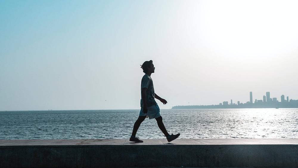 chàng trai đi bộ bên bờ biển