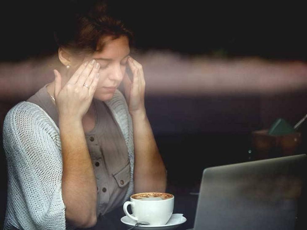 cô gái đau đầu bên cốc cafe và máy tính
