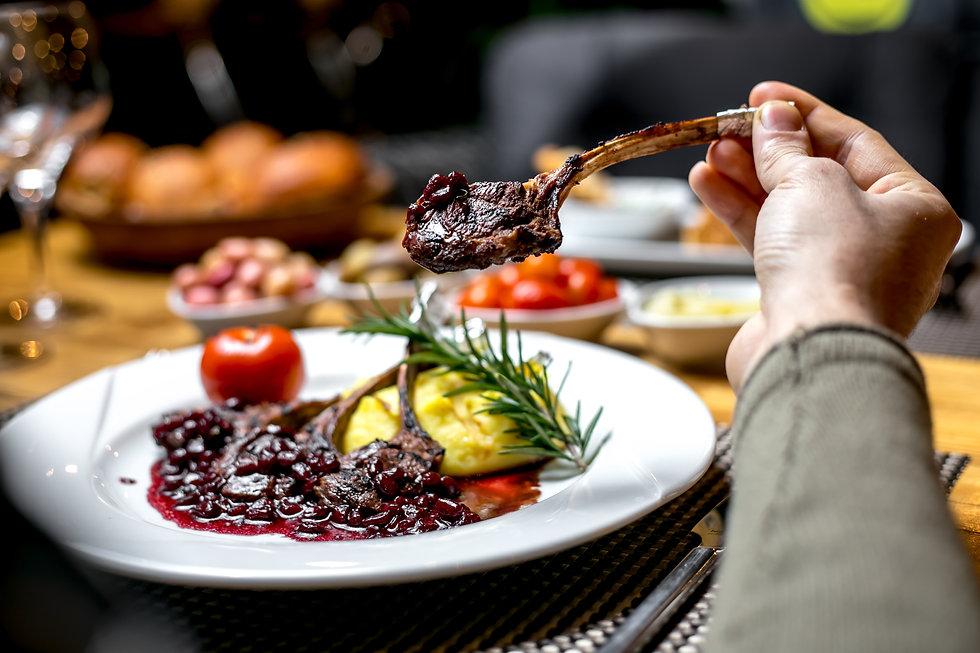 front-view-man-eats-fried-lamb-ribs-pomegranate-sauce.jpg