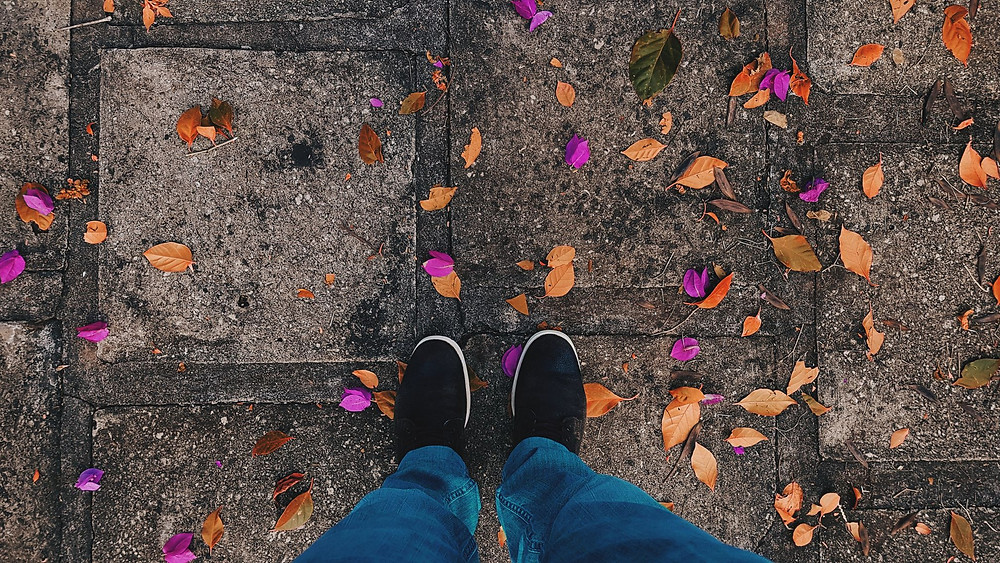 Feet on pavement surrounded by autumnal leaves.