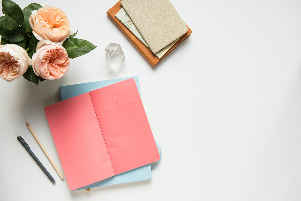 Notebooks and roses on a white desk