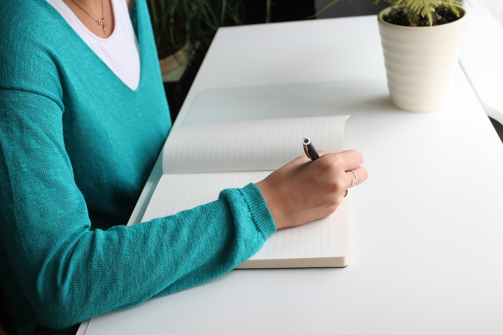 A woman in a blue jumper writing in a notebook at her desk with a plant in a white pot sitting on top.