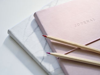 Two coloured pencils on two notebooks on a white desk.