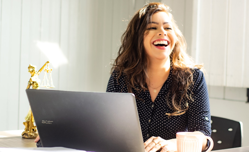 Smartly dressed woman laughing as she sits at her laptop on her desk.