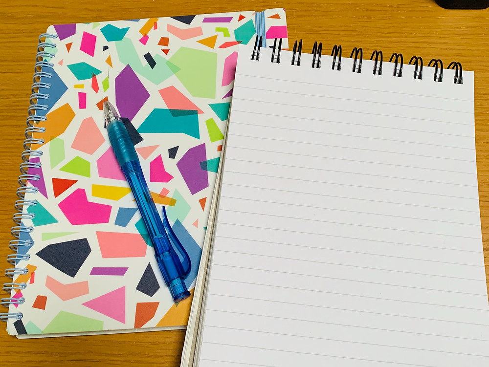 A colourful notebook and an open notebook with a blue pen.
