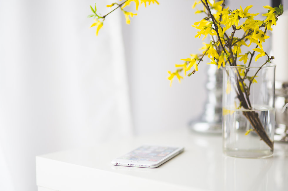 iPhone 6 plus on a white desk with a vase of yellow flowers