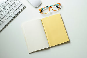 A white and yellow notebook, a pair of yellow spectacles and a white computer and mouse on a white desk.