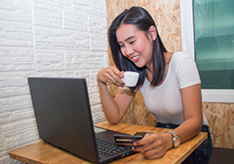 A woman drinking coffee while on a laptop