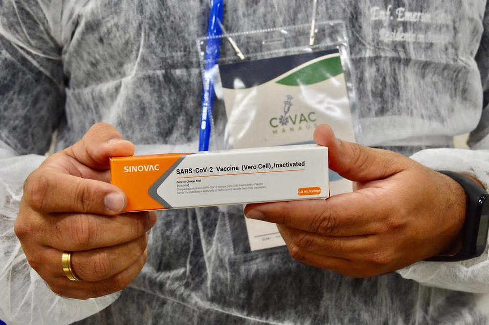 Mão segurando caixa de vacina CoronaVac.