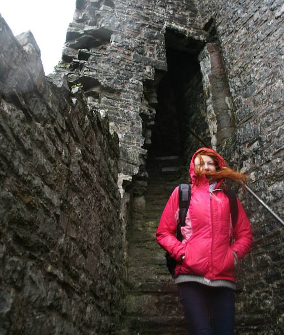 red haired woman in pink coat descending ruins