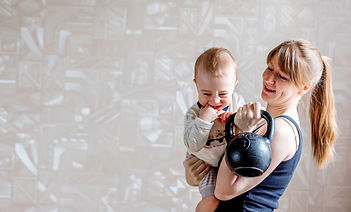 Sportive mother with cute baby and kettl