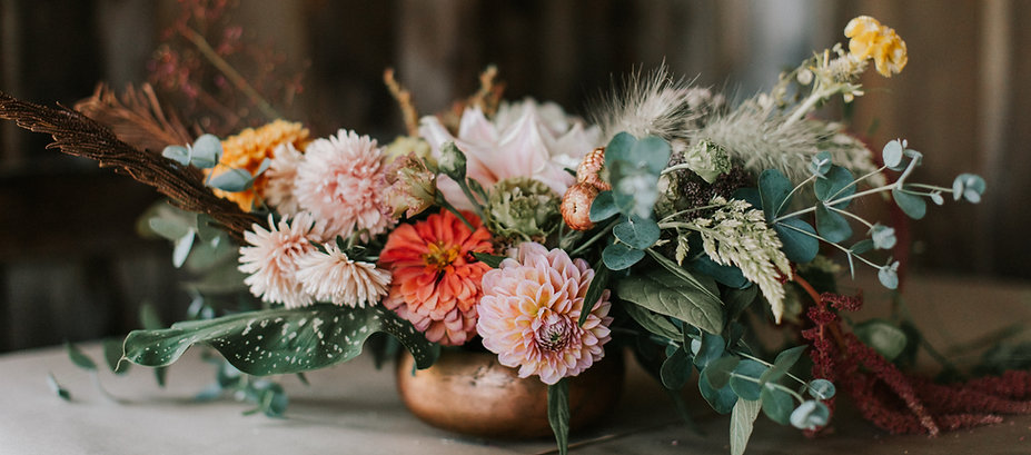 a coppr pot full of flowers in sunset tones. photo by Jamie Mercurio