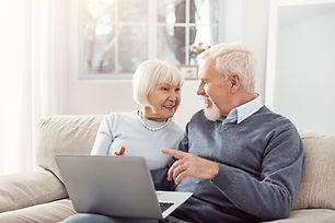 sharing-opinions-joyful-senior-husband-wife-sitting-sofa-living-room-discussing-article-to