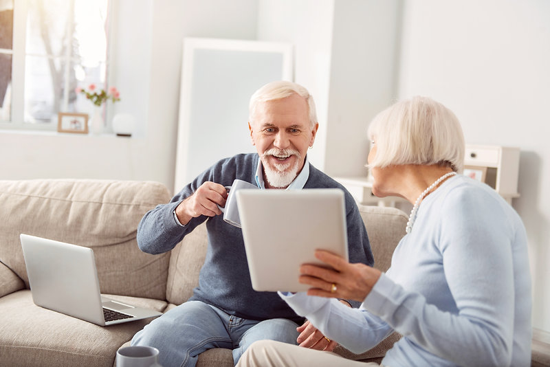 check-it-out-pleasant-elderly-woman-showing-her-husband-tablet-with-open-news-article-it-m