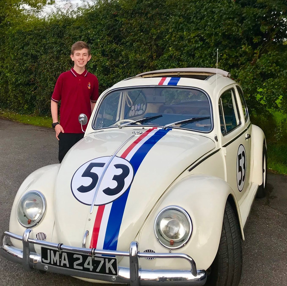 Daniel stood by a white car with red,blue and white stripes and the number 53 on the front