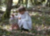 petite fille en robe blanche sur-mesure qui joue dans la forêt avec une cage à oiseaux