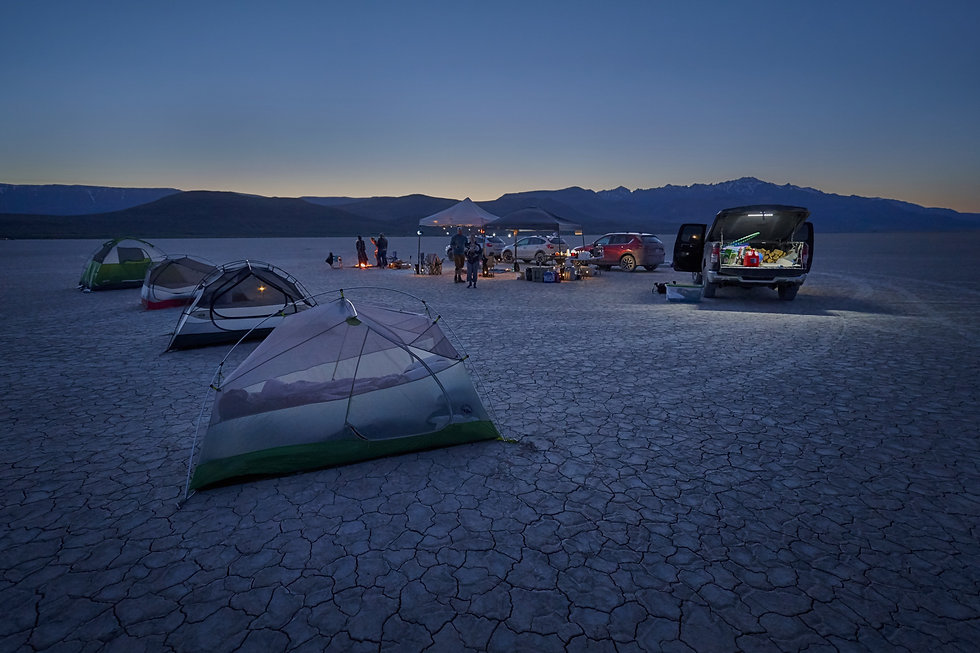 A group of people are car camping in the desert, tents are set up for a sunset gathering