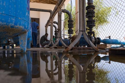 Des ouvriers travaillent sur une station de pompage qui recycle les eaux usées de la station d'épuration de Douda pour irriguer des parcelles cultivables.