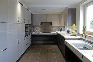 Long wheelchair accessible kitchen designed by Adam Thomas in beige gloss and dark wood.