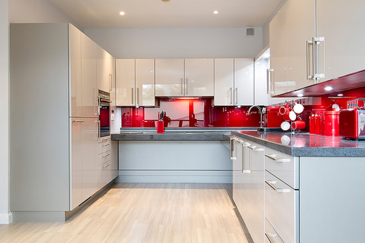 Wheelchair accessible kitchen in white gloss acrylic with red glass splashbacks by Adam Thomas for Roundhouse Design