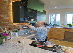 Adam Thomas, accessible kitchen designer, preparing food in a fully accessible kitchen designed by A