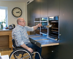 Inclusive, wheelchair accessible kitchen designed by Adam Thomas for Roundhouse Design in dark teal