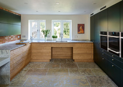 Wheelchair accessible kitchen by Adam Thomas for Roundhouse Design in river washed ply and dark teal