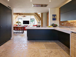 Large multi-generational kitchen by Adam Thomas for Roundhouse Design in dark teal matt lacquer and